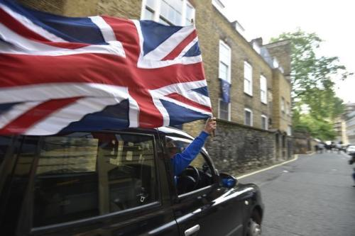 A taxi driver holds a Union flag, as he celebrates following the result of the EU referendum, in central London